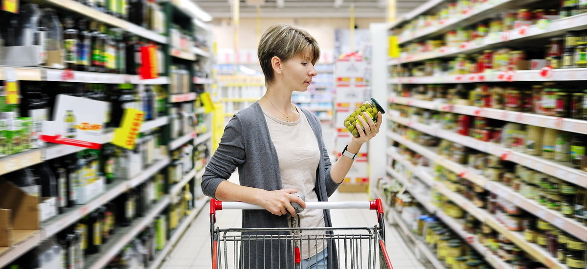 Images of a woman pushing a trolley in a food aisle and examining a food label
