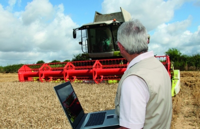 Man in field with laptop, next to a combine.